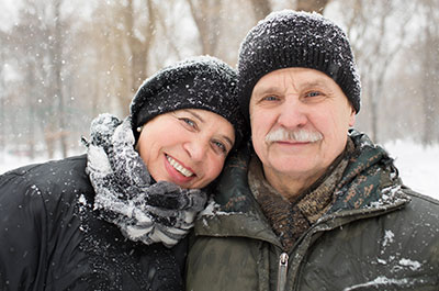 older couple standing in the snow