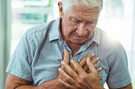 older man holding his chest