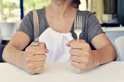 woman holding a knife and fork