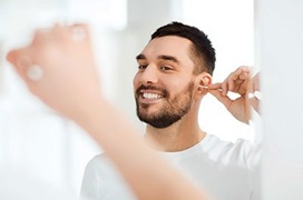 man cleaning his ears