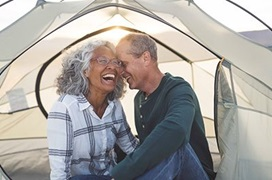man and woman laughing in a tent