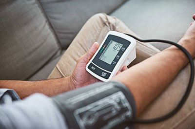 Man taking blood pressure at home