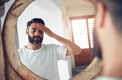 man looking in mirror rubbing forehead