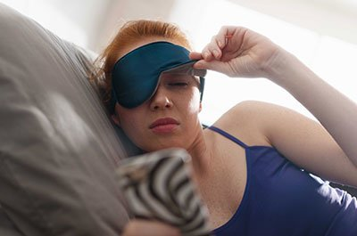 woman with sleep mask in bed