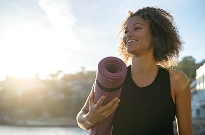 woman holding a yoga mat