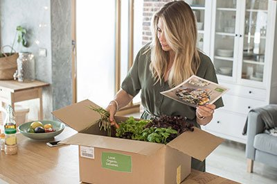 Woman opening meal kit box and reviewing recipe