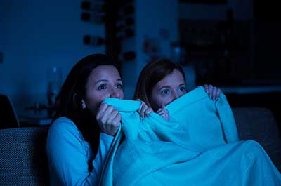 two women watching a scary movie