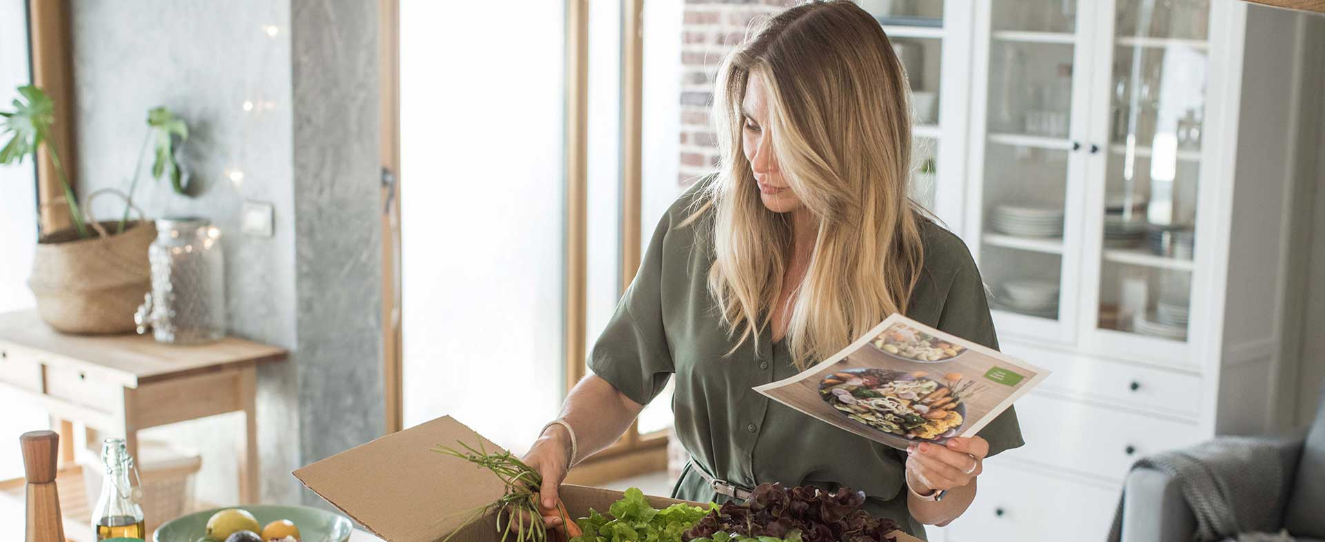 Woman opening meal kit and reviewing recipe
