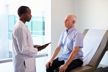 man talking with doctor at wellness visit