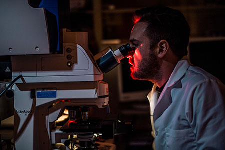 cancer researcher looking in microscope