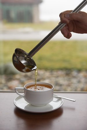 Cup of bone broth soup being poured from silver ladle