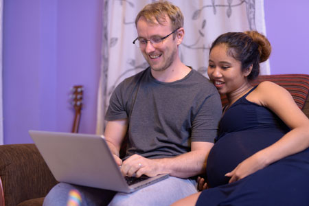 pregnant couple looking at laptop