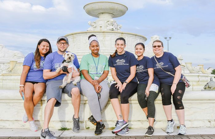2019 Clinical Trial Team sitting on a fountain with a dog