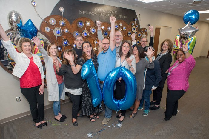 group celebrating lives of 10 year glioblastoma survivors with balloons shaped like number 10