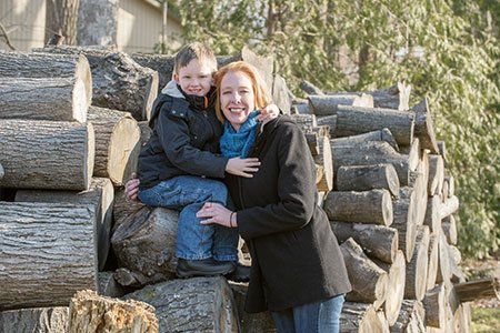 breast cancer patient erika lojko posed on wood pile with her son