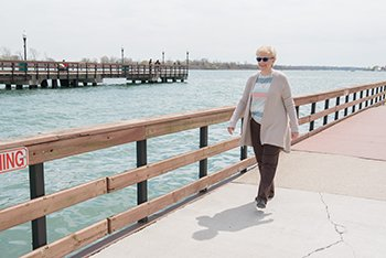 Spine patient Beverly walking by the detroit river