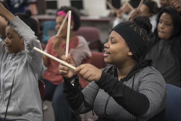 girls using drumsticks to make music